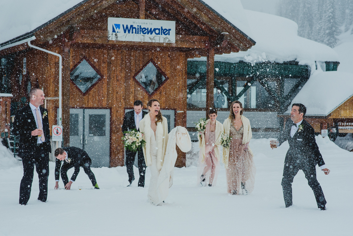wedding party plays in the snow at whitewater ski resort