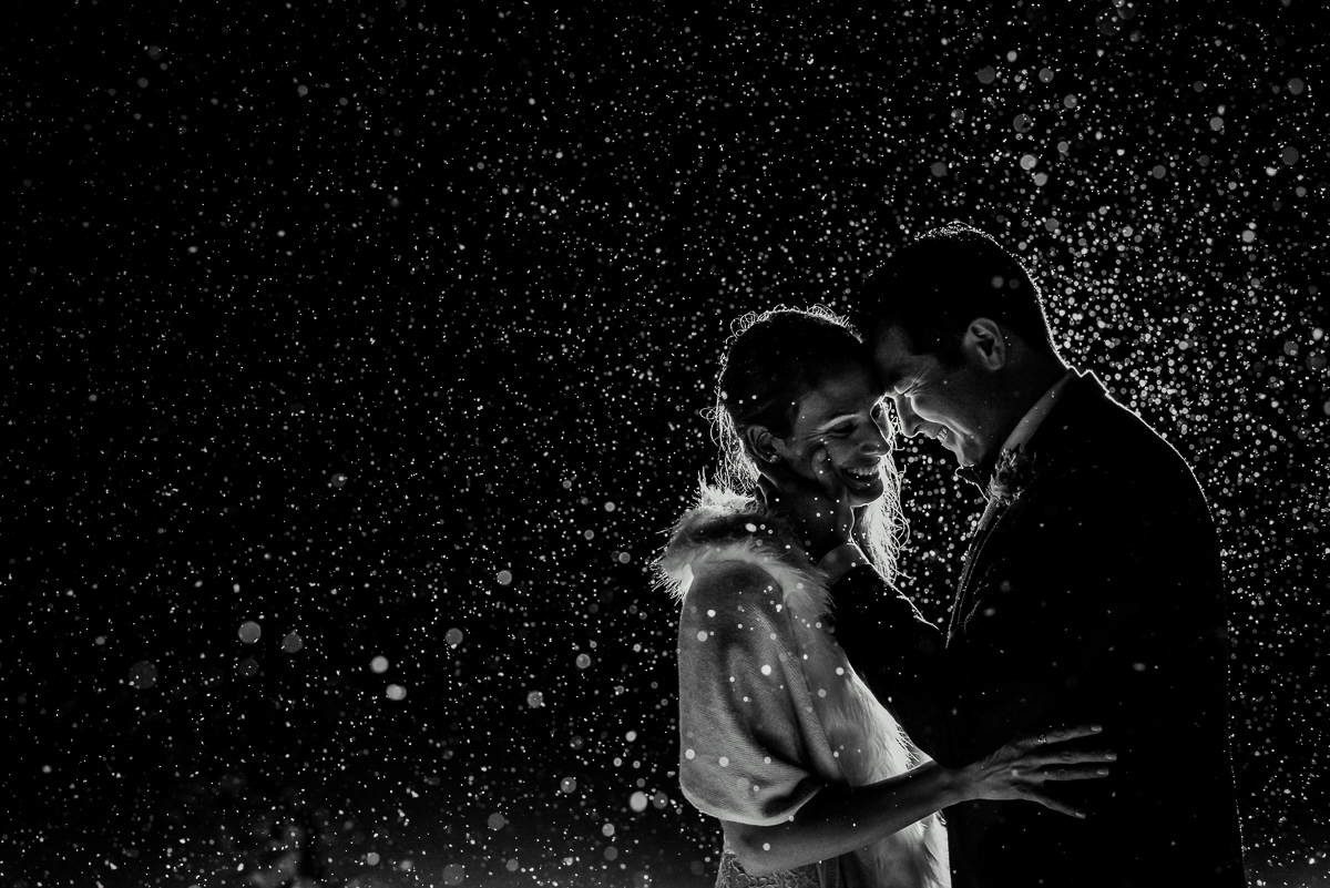 Bride and groom laugh during their rainy day wedding at Whitewater Ski Resort