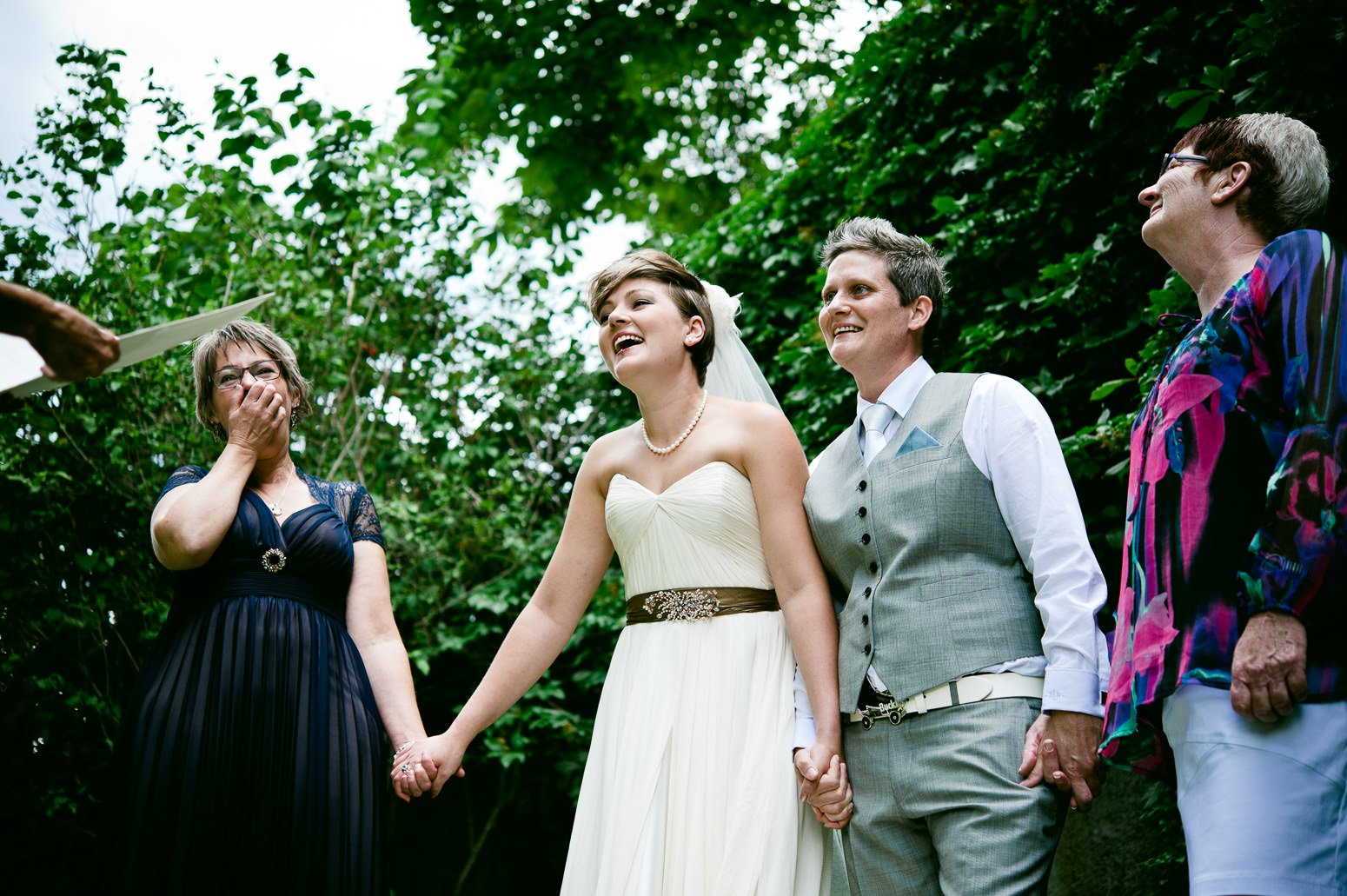 Two brides laugh during their nelson bc wedding ceremony