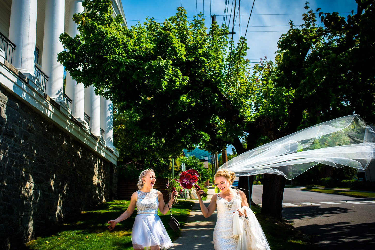Twin bridesmaid laughs at brides veil caught in the wind at her nelson bc wedding