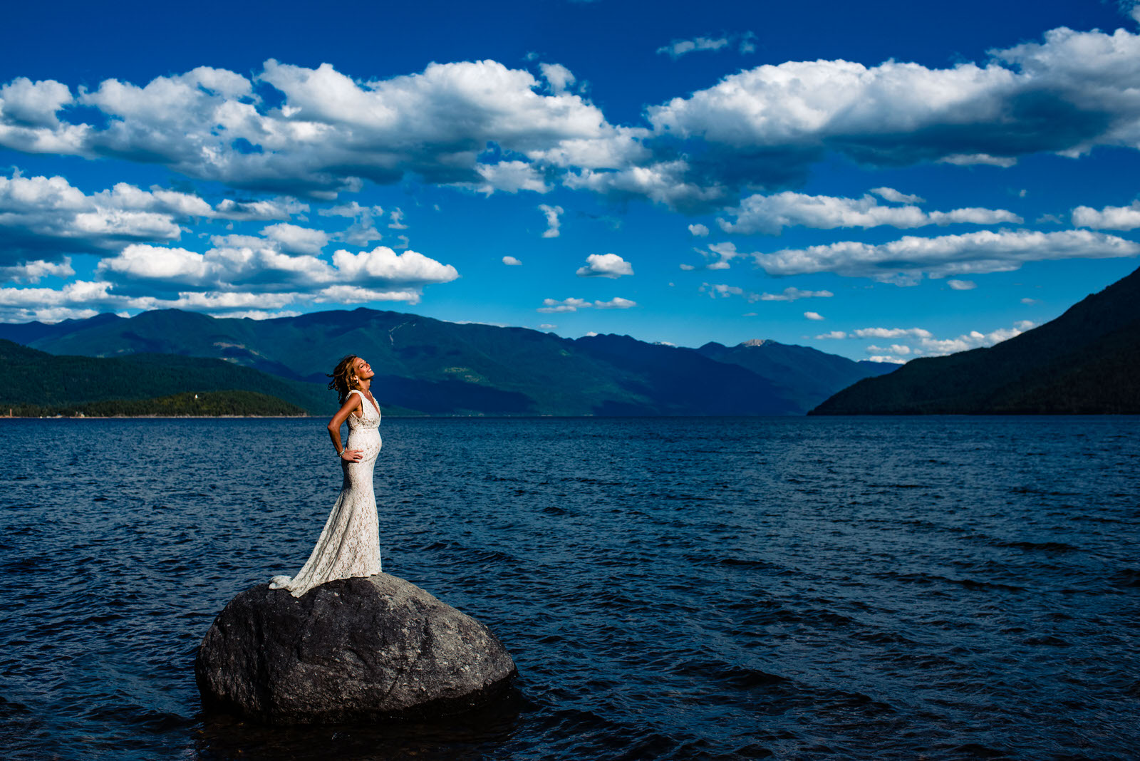 Pregnant bride stands on a rock in kootenay lake at her nelson bc wedding