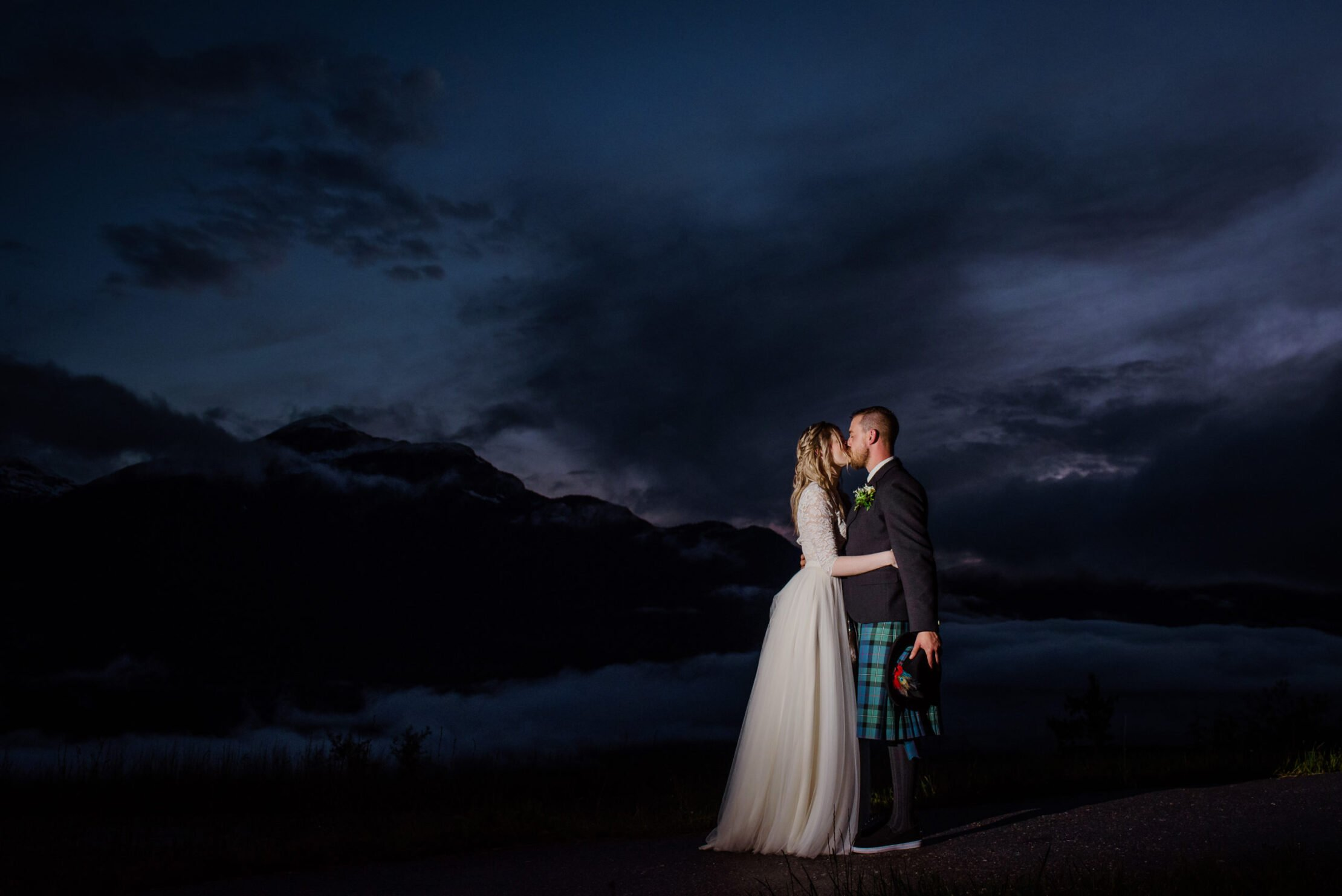 Bride and groom kiss in the stormy sky above Revelstoke Mountain resort