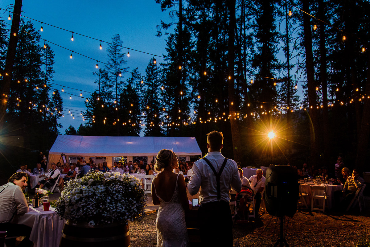 bride and groom give a toast at dusk with strings lights at their christina lake wedding