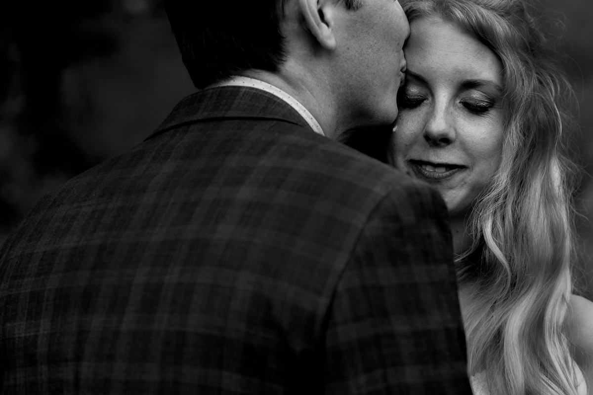 bride cries as groom kisses her forehead during nelson bc wedding