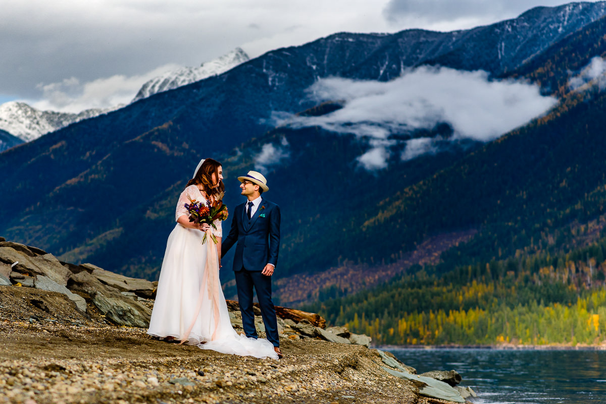 Bride and groom elope on the shore of kootenay lake with fall colours behind them