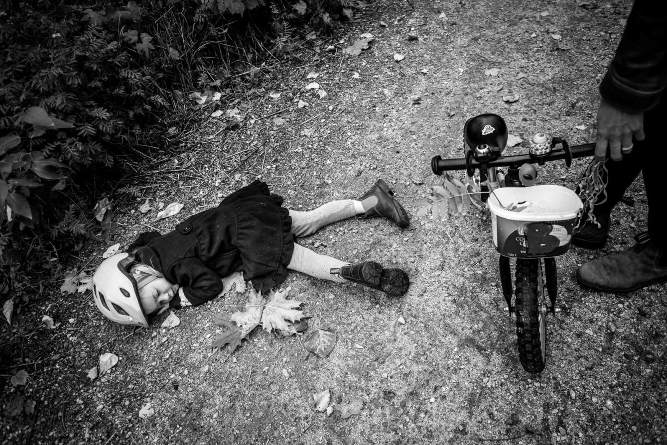 girl lays on the ground beside her bike