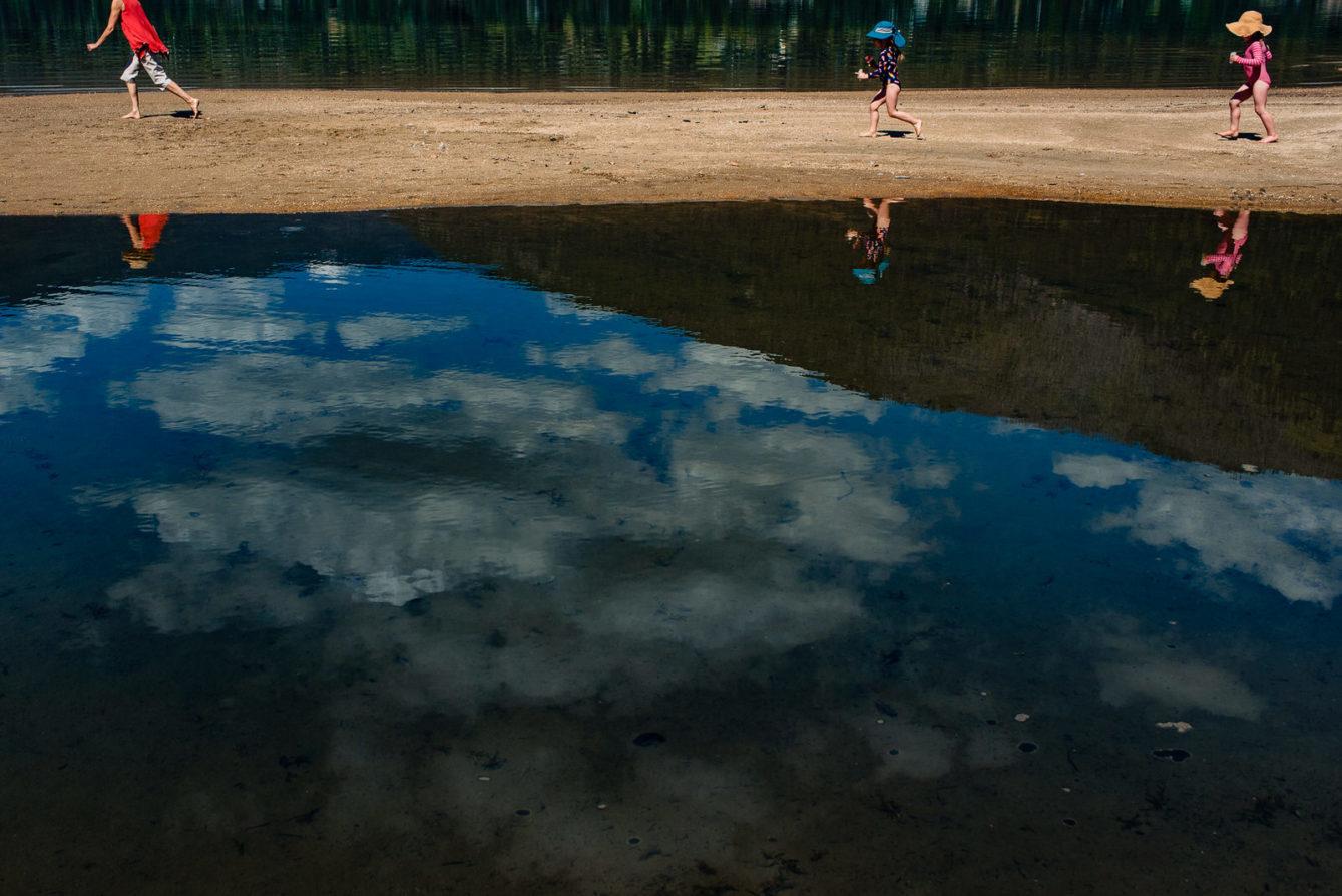 Girls follow their grandma along the shore of kootenay lake in nelson bc family photo
