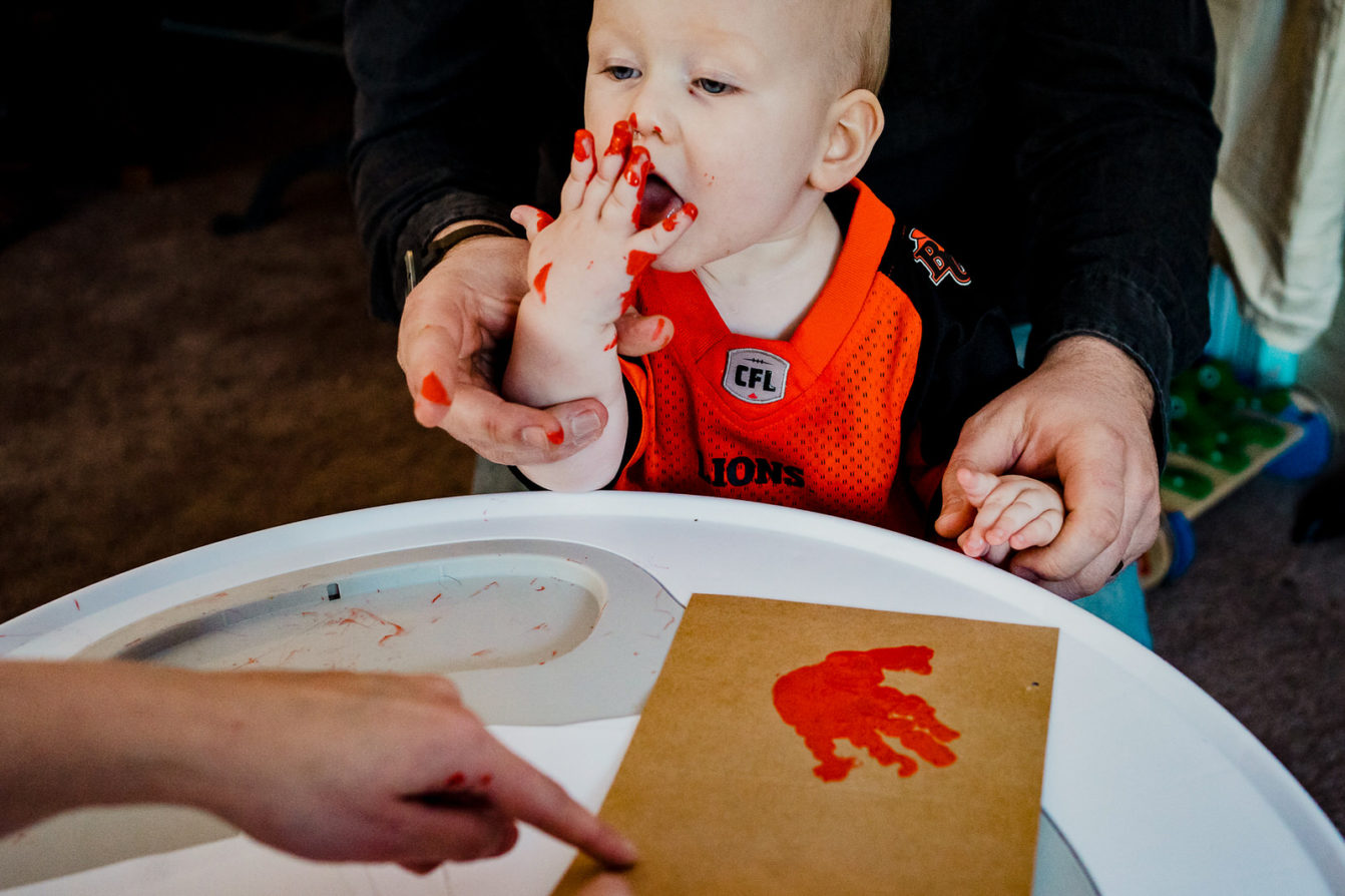 Boy eats paint off his hand while finger-painting in nelson bc family photo