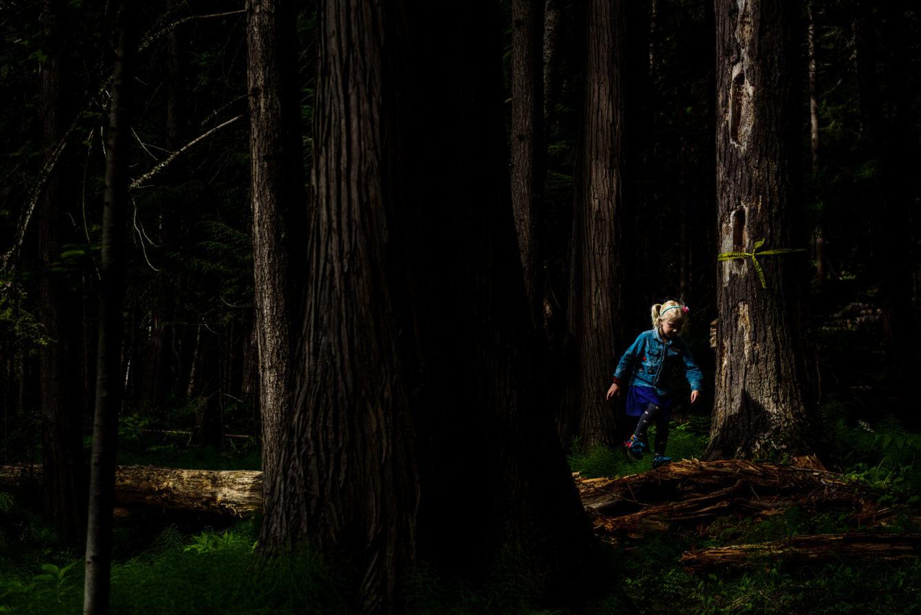 girl walks in a beam of light among trees
