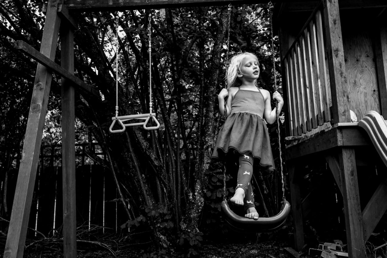 girl stands on swing in environmental portrait