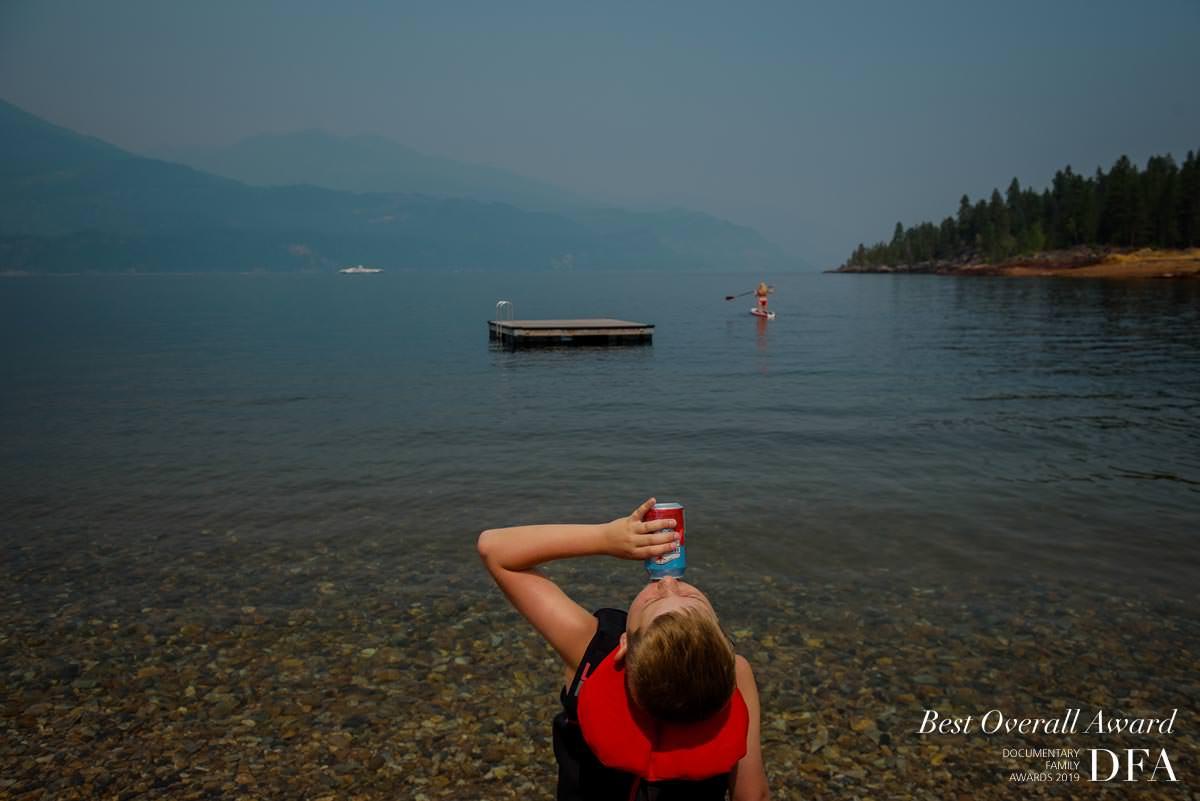 Boy drinks soda in documentary family photo award photo on kootenay lake