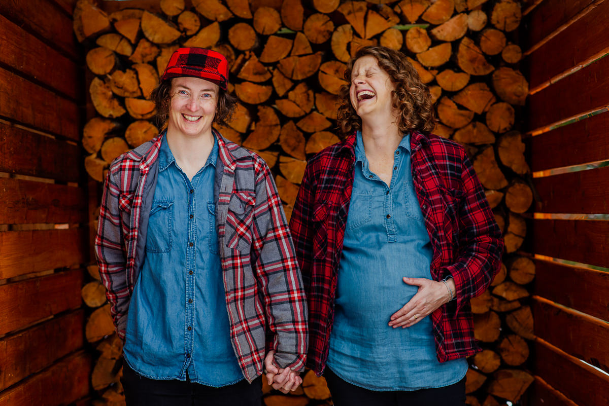 Two women laugh in front of log pile in nelson bc family photo