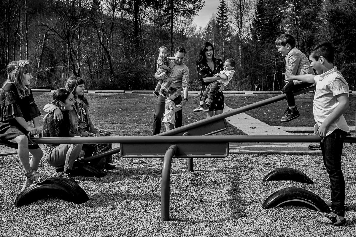 multiple family members play on the teeter totter in a nelson bc family photo