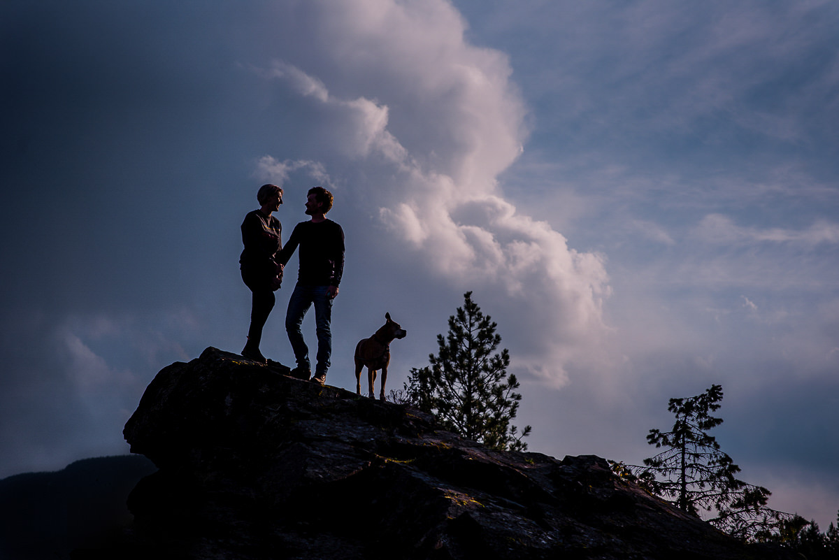 Couple silhouetted agains purple clouds with their dog in engagement photo near nelson bc