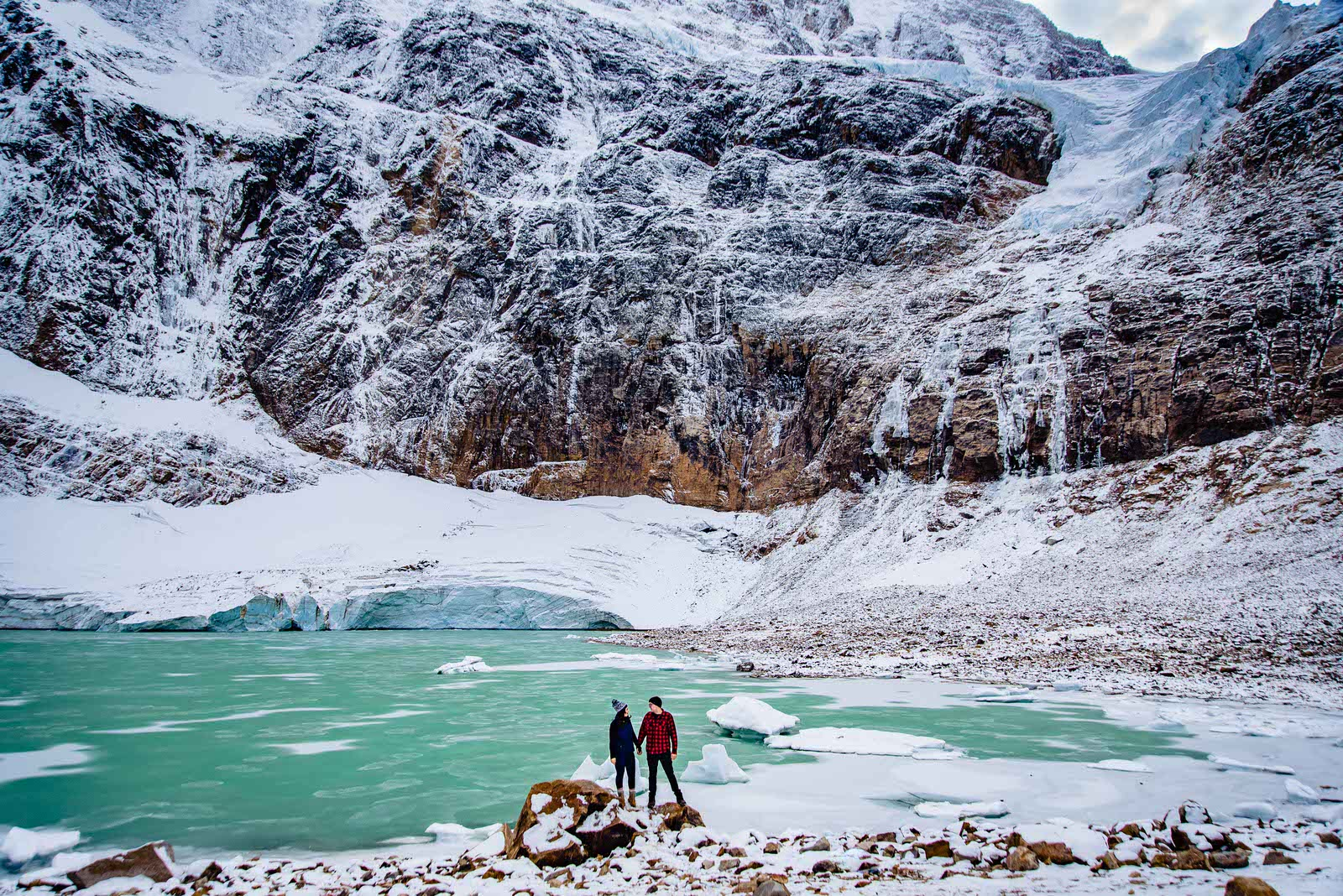 couple holds hands in front of mount edith cavell glacier in jasper national park engagement photo