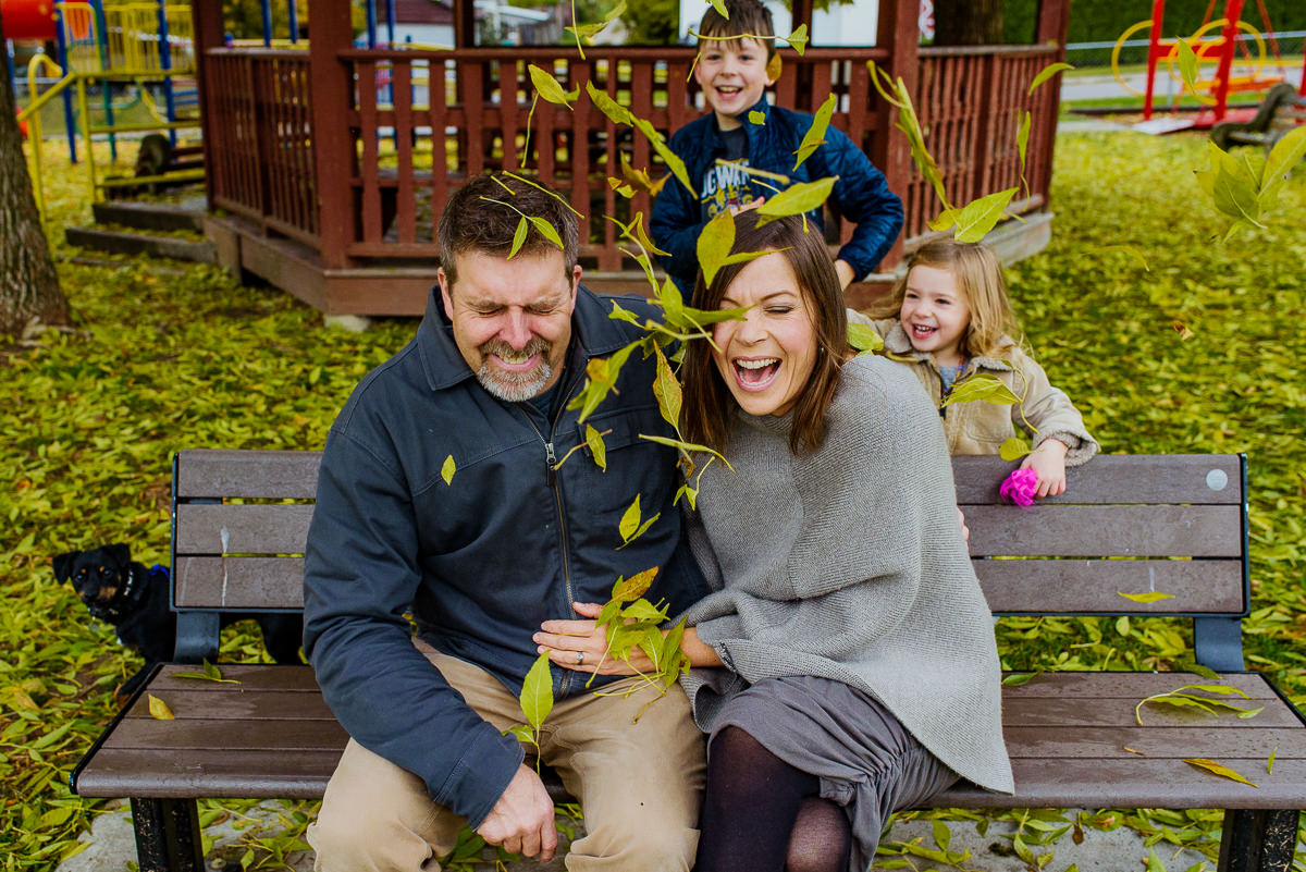 kids throw leaves at their parents during nelson bc family photo in lion's park