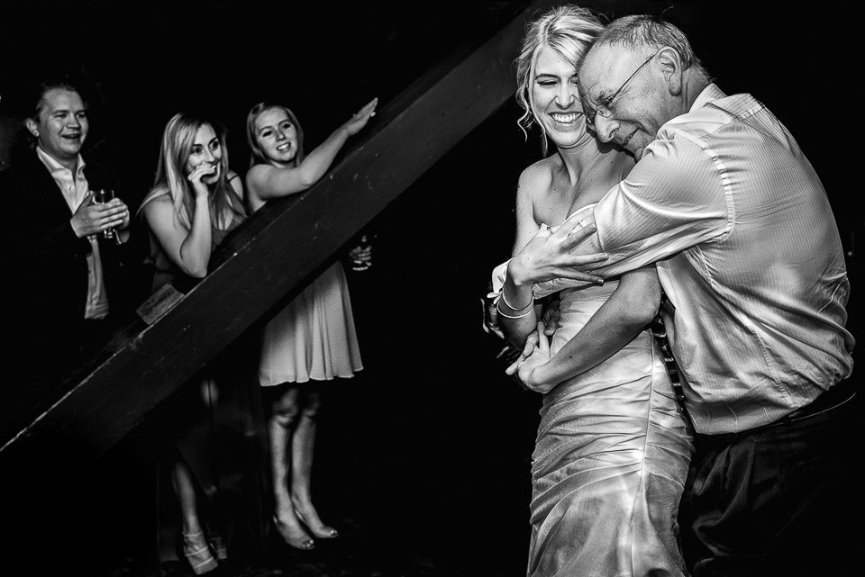 dad hugs his daughter after their first dance at her red mountain resort wedding reception at rafter's pub