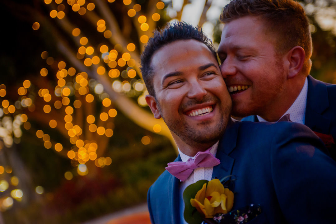 two grooms embrace at their disneyland wedding