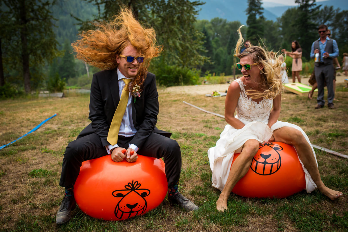 bride and groom race on bouncy balls at their nelson bc wedding