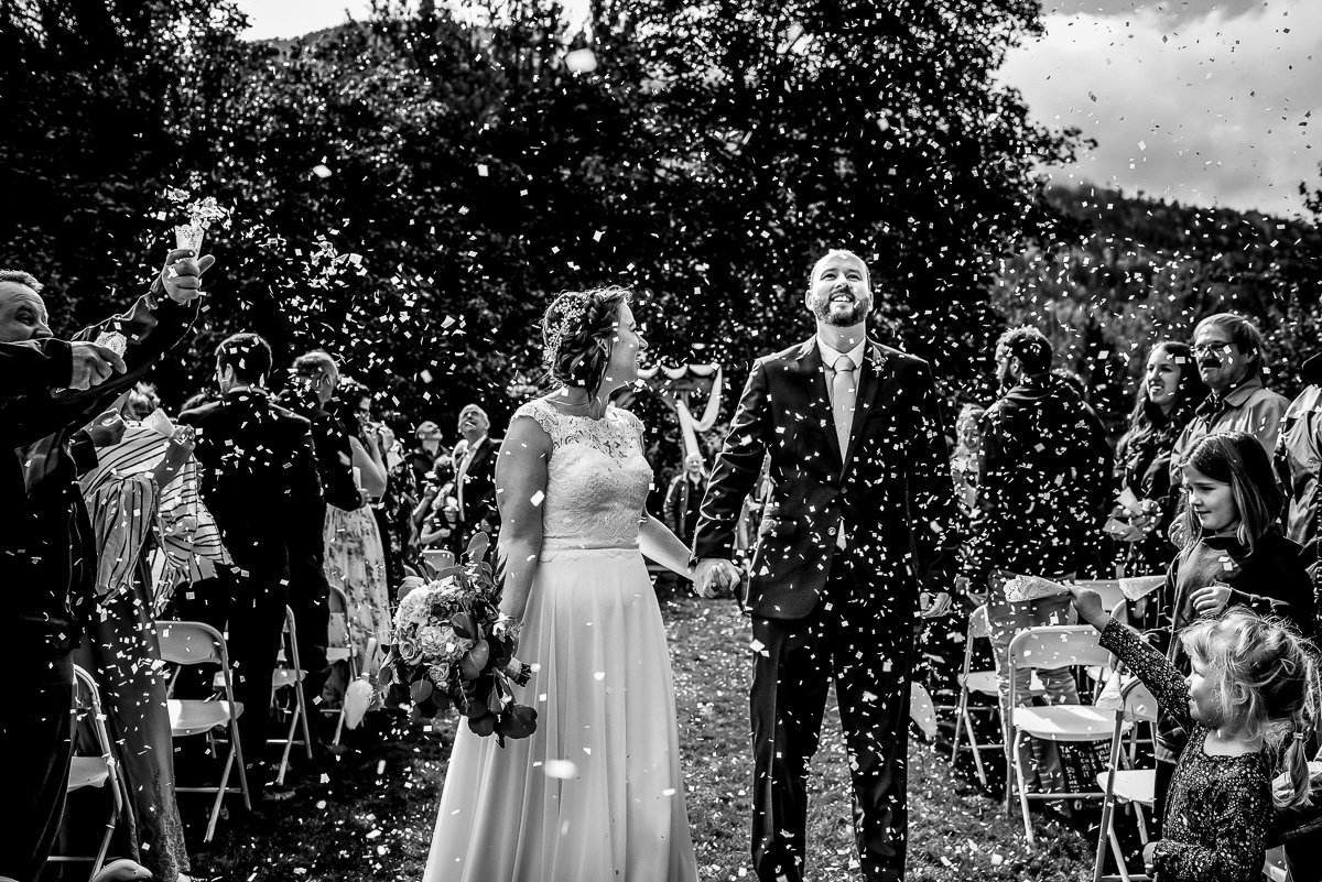 Bride and groom look up at the sky as confetti rains down after their Georama Growers wedding ceremony