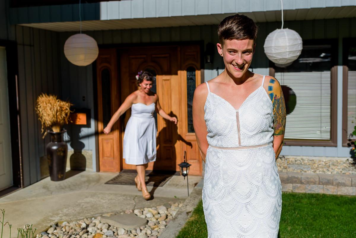 bride tries to peek behind her as her bride sneaks behind her