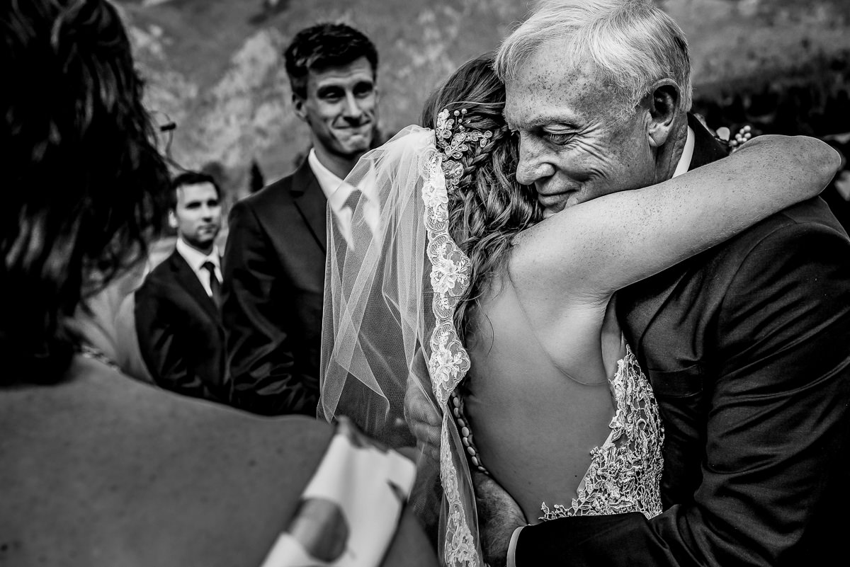 Dad hugs his daughter as groom smiles at their Bull River Guest Ranch wedding