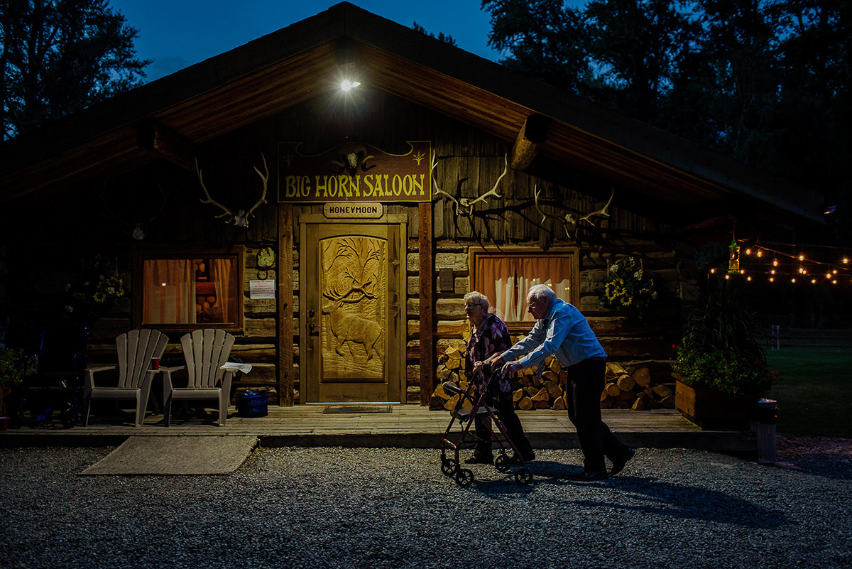 Old couple walks past honeymoon suite at Bull River Guest Ranch Wedding