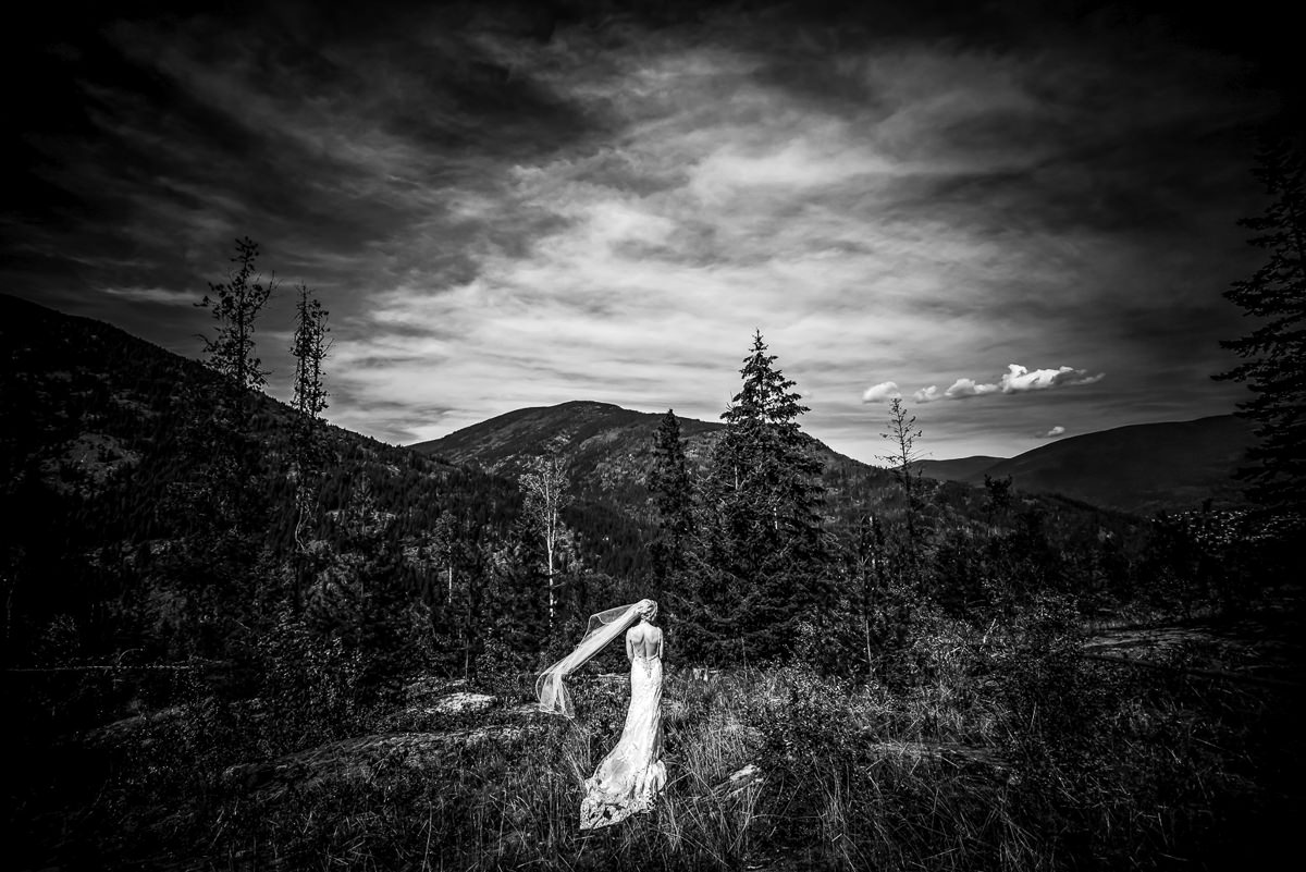 Bride stands on a mountainside during her nelson bc wedding
