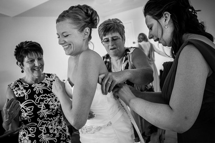 bride laughs as she puts on her wedding dress at Kootenay Lakeside resort