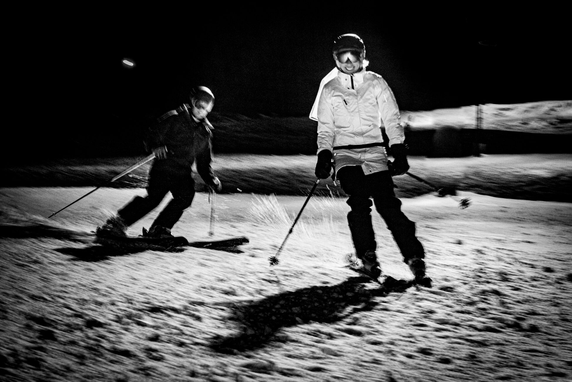 Bride and groom ski at night