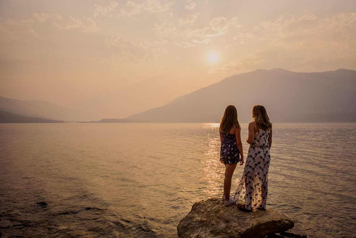 Two sisters standing on an outcropping of rock in kootenay lake