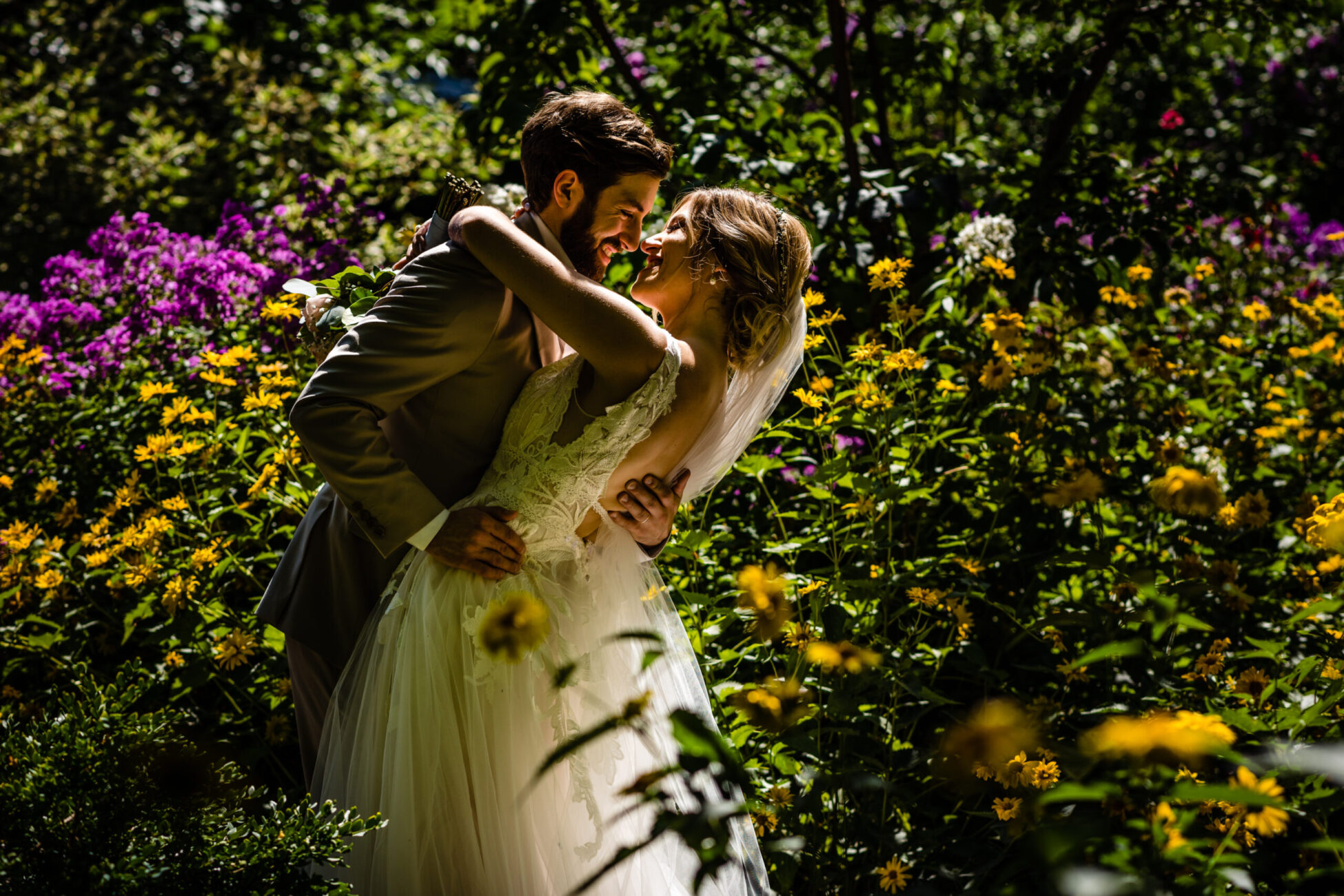 Bride and groom embrace in the flowers at linden gardens wedding
