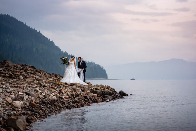 Couple stands on the shore of upper arrow lake at their halcyon hot springs wedding