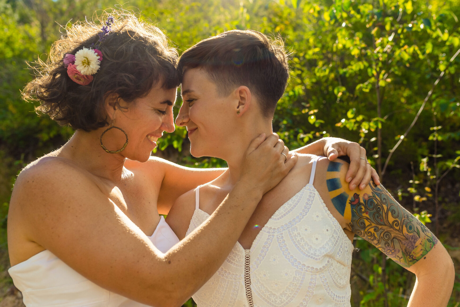 Two brides embrace in the setting sun by kootenay wedding photographer bobbi barbarich